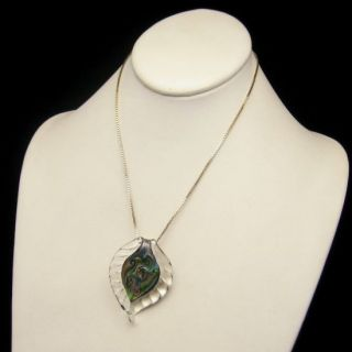 pendant necklace that features a large leaf shaped glass pendant