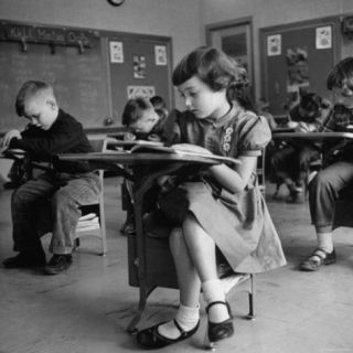 Cute Little Girl Busily at Work, Sitting in a Desk Chair in a Schoolroom, Other Pupils at Work Too Photographic Print by Gordon Parks