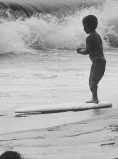 Little Boy Standing on a Surf Board Staring at the Water Photographic Print by Allan Grant