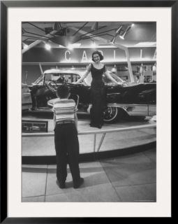 Model Posing Beside Cadillac Eldorado Captures Attention of Young Boy at National Automobile Show Pre made Frame