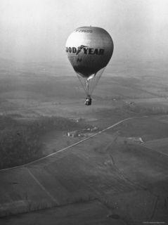 Good Year Hot Air Balloon Flying to New Philadelphia Premium Photographic Print by John Phillips