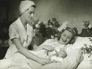 Mother Lying in Bed Smiling To Baby Child, Nurse Standing Beside Photographic Print by George Marks