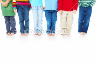 Portrait of kids feet standing in row against white background