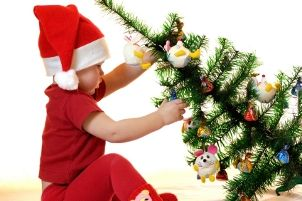 Baby pulling over a Christmas tree decorated with baby toys